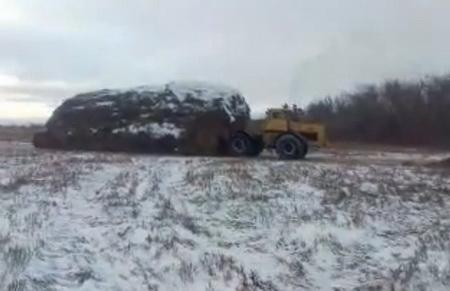 Несколько тракторов везут копну соломы